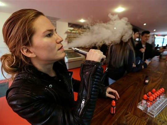 In this Feb. 20, 2014 photo, Talia Eisenberg, co-founder of the Henley Vaporium, uses her vaping device in New York. Soon, the Food and Drug Administration will propose rules for e-cigarettes. The rules will have big implications for a fast-growing industry and its legions of customers.