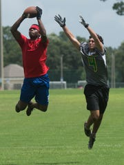 Catholic High School's Bryce Yates, right, reaches out for the end zone grab against the Pine Forest High School defense during a 7 on 7 football tournament at Ashton Brosnaham Sports Complex Friday morning June 30, 2017.
