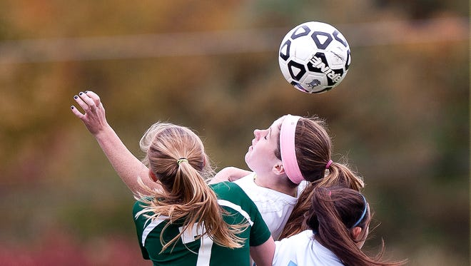 Mount Mansfield's Anna Burke, center, wins a header above teammate Macey Wissell (13) and St. Johnsbury's Grace Cooke during the second half of Saturday's girls soccer game in Jericho.