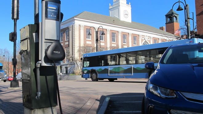 A public bus passes an electric-car charging station on Aprili 28, 2016, at Church and Main streets in Burington.