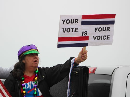 A woman urges voters to cast their ballot.