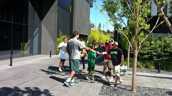 Oregon offensive lineman Tyler Johnstone signs autographs and talks with fans Saturday after practice.