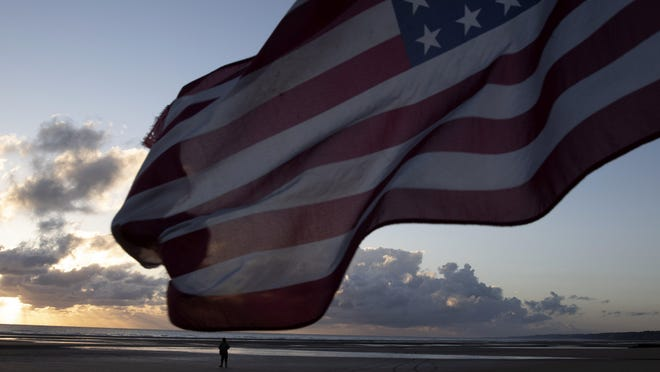A man in a vintage US WWII uniform walks at sunrise prior to a D-Day 76th anniversary ceremony in Saint Laurent sur Mer, Normandy, France, Saturday, June 6, 2020. Due to coronavirus measures many ceremonies and memorials have been cancelled in the region with the exception of very small gatherings.