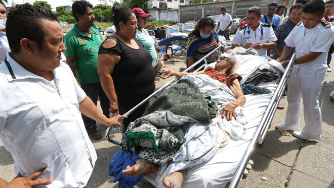 Evacuated patients lie on their beds outside the hospital in the aftermath of a massive earthquake, in Juchitan, Oaxaca state, Mexico,  Sept. 8, 2017.