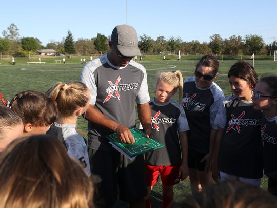 Missfits Xtreme under 11 girls team assistant coach Randy Tate, center, talks to members of the team Wednesday at the Redding Soccer Park.