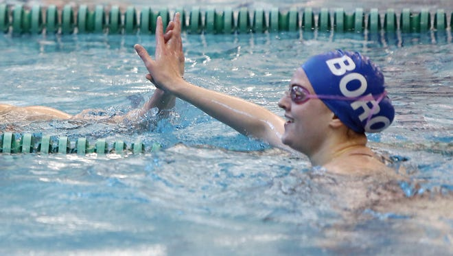 Ursuline's Emily Slabe gives a high-five to Springboro's Hannah Whiteley after the  girls 100 yard backstroke.