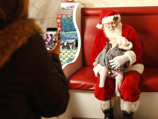 Isla Cannon poses for a picture with Santa after the