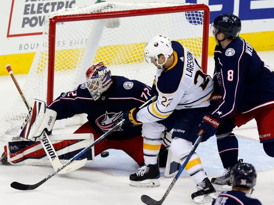 Columbus Blue Jackets goalie Sergei Bobrovsky, left, of Russia, stops a shot against Buffalo Sabres forward Johan Larsson, center, of Sweden, as Blue Jackets defenseman Zach Werenski defends during the third period of an NHL hockey game in Columbus, Ohio, Wednesday, Oct. 25, 2017. The Blue Jackets won 5-1. (AP Photo/Paul Vernon)