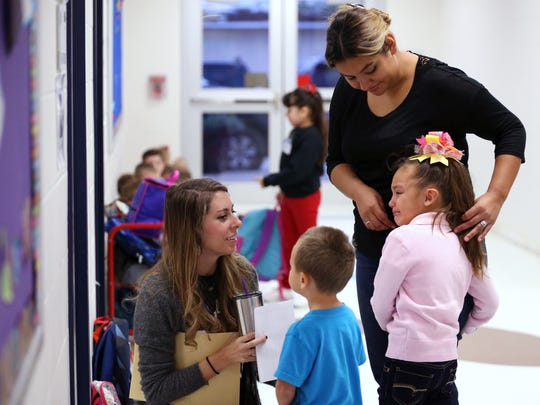 Kindergarten teacher Ashley Moeckel (left) tries to calm her student, Hailey Stiles, 5, as her mom, Marlene Stiles, and brother Edgar Stiles III, 3, drop her off for school at the combined Live Oak Learning Center and Little Bay Primary on Wednesday, Oct. 11, 2017, in Rockport. Little Bay Primary is expected to reopen around Christmas after undergoing damage from Hurricane Harvey.