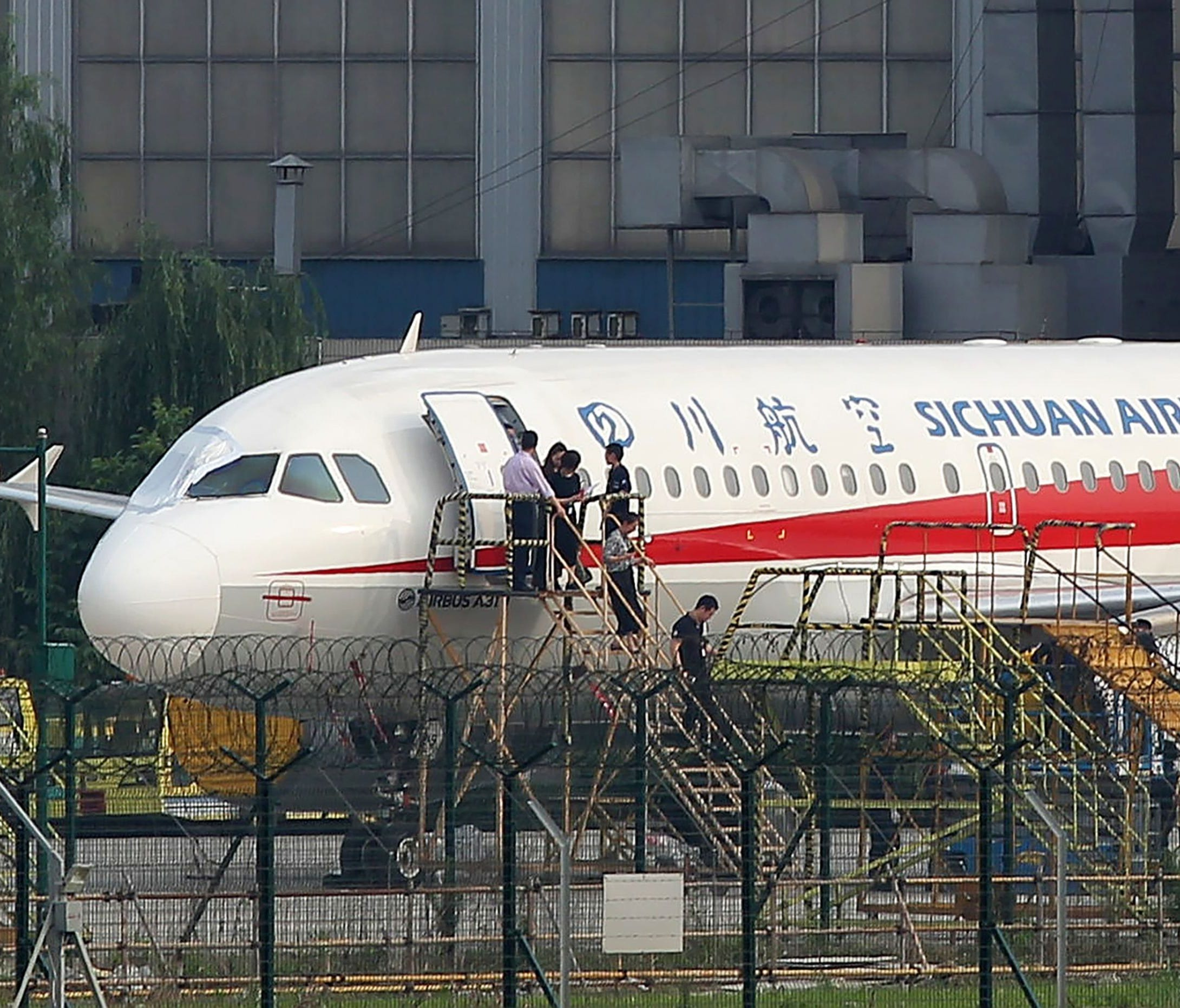 Sichuan Airlines employees check an Airbus A319 on May 14, 2018, after an emergency landing, as a broken cockpit window is covered, in Chengdu in China's northwestern Sichuan province.   The pilot who made an emergency landing in southwest China after