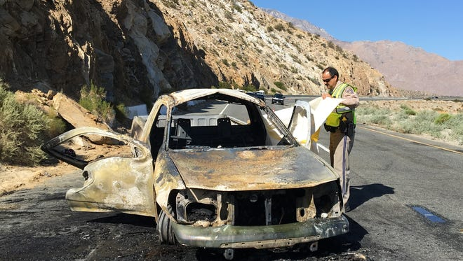 California Highway Patrol Officer John Quintero adjusts a tarp covering the victim of a pickup fire. The fire happened Sunday morning on Highway 111, west of Palm Springs.
