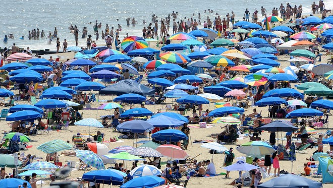 Umbrellas and beachgoers fill Rehoboth Beach on Labor Day weekend 2013. The beach was last renourished the year after  Hurricane Sandy hit in October 2012.