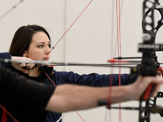 Darin Watts and Alexis Serbert practice their archery