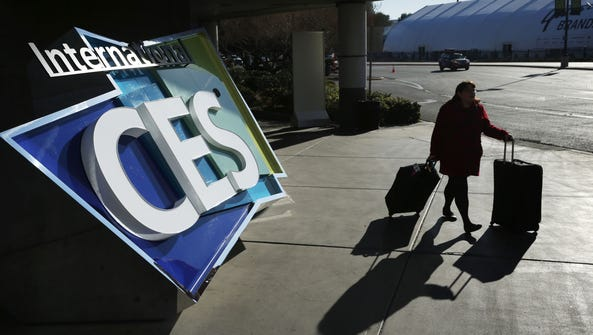 A woman walks by an International CES sign at the Las