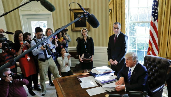 President Donald Trump, accompanied by Intel CEO Brian Krzanich, speaks to members of the media during his meeting in the Oval Office of the White House in Washington, Wednesday, Feb. 8, 2017. Krzanich announced a $7 billion investment in advanced factory in Chandler, Ariz.