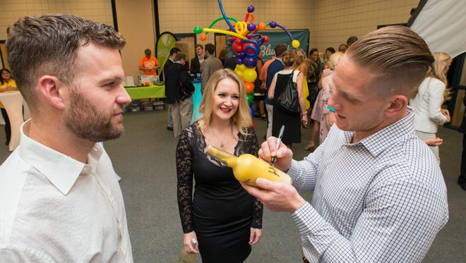 Matt Flynn, left, looks on as fellow NFL player AJ Hawk signs an autograph during the Light Up Learning event at the Sanders Beach-Corinne Jones Resource Center in Pensacola on Thursday, June 22, 2017.