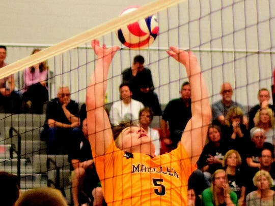 Moeller's Andrew Luers sets up a spike for the Crusaders