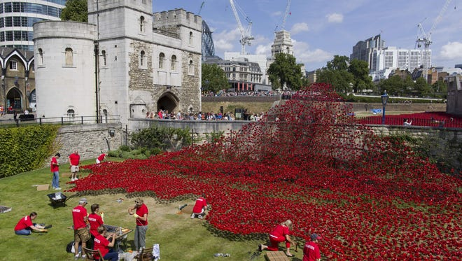 """Volunteers install ceramic poppies as part of the art installation """"Blood Swept Lands and Seas of Red"""" by artist Paul Cummins."""