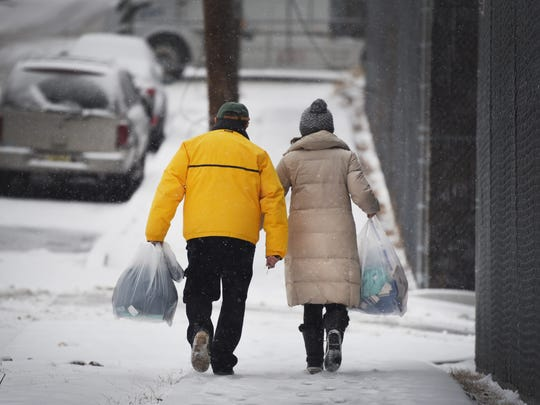 A couple walk side by side carrying bags as snow falls