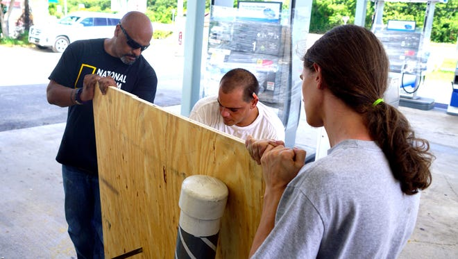Yojan Ramos cuts a piece of plywood to cover a window of the Key Largo Chevron gas station owned by Ray Ochoa, left.  Michael Johnson also helps.