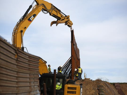 Workers replace sections of the border wall, left, with new sections, right, Tuesday, Jan. 8, 2019, in Tijuana, Mexico. Ready to make his case on prime-time TV, President Donald Trump is stressing humanitarian as well as security concerns at the U.S.-Mexico border as he tries to convince America he must get funding for his long-promised border wall before ending a partial government shutdown that has hundreds of thousands of federal workers facing missed paychecks. (AP Photo/Gregory Bull)