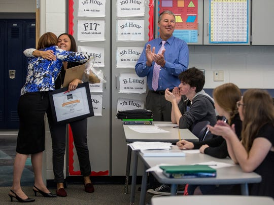 Christine Shigley gets a hug from Brenda Tenniswood, director of administrative services at RESA, after being surprised with the Distinguished Teacher award and $300 for a classroom makeover Tuesday, May 10, 2016 at Marysville High School. St. Clair County RESA will continue the Distinguished Teacher award once a month for teachers throughout the county.