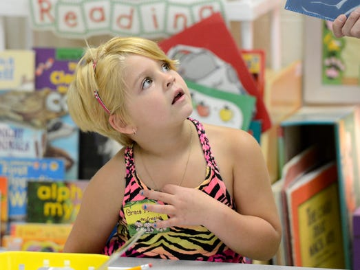 Grace Fleming listens to Mountain Home Kindergarten teacher Kim Crecelius on Wednesday during the first day of classes.