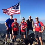 Several Treasure State Trail Runners pose with Old Glory atop Highwood Baldy on Independence Day.