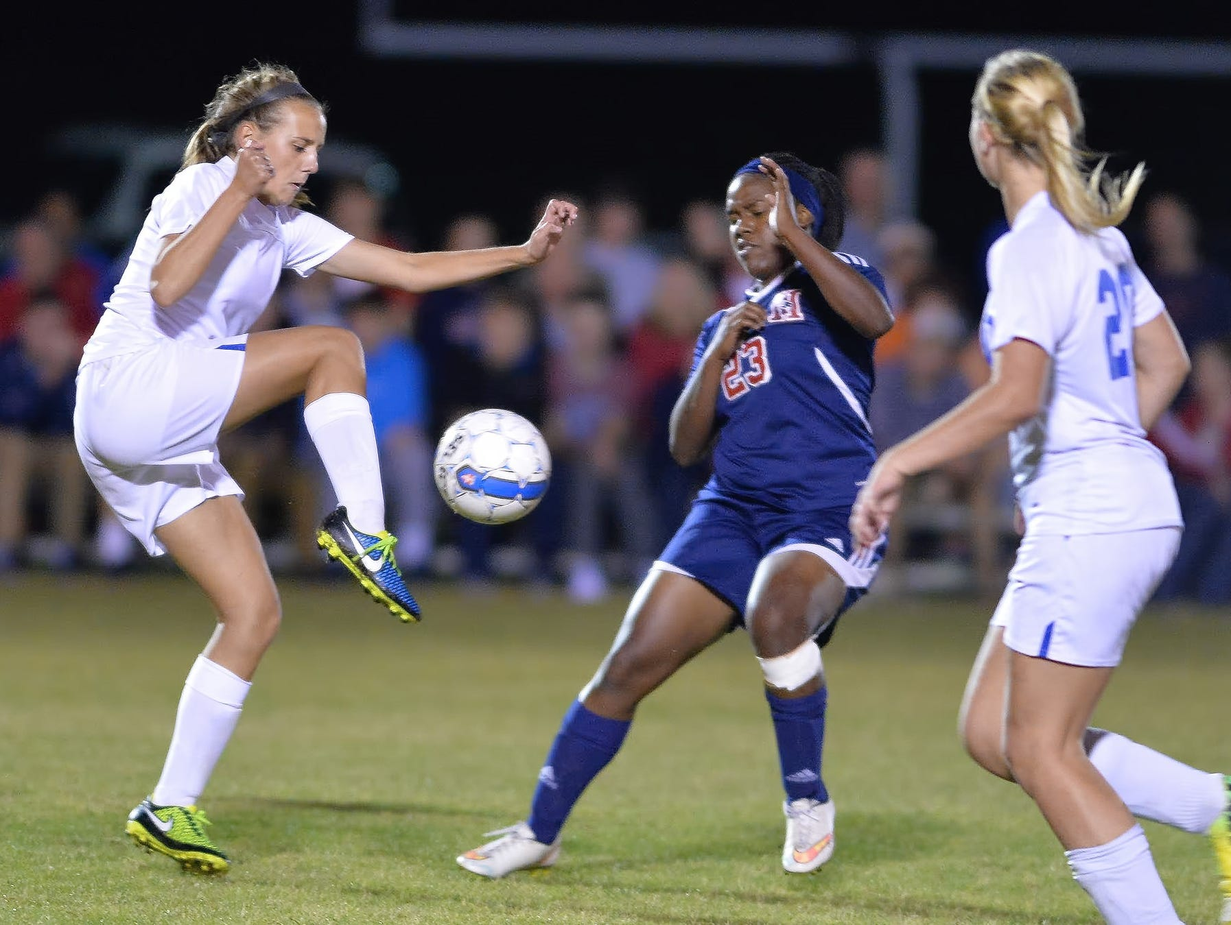 White House High freshman defender Allyson Trimmer plays a ball out of the air in front of White House Heritage senior Faith Williamson.