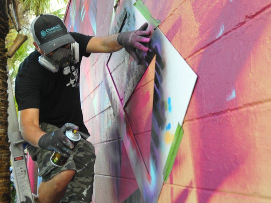 Miami artist and muralist Jay Bellicchi works on a