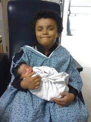Christian Pittman holds his newborn nephew. In April