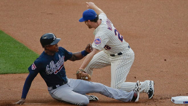 Mets second baseman Daniel Murphy tags out the Braves' B.J. Upton as he attempts to steal second base in the first inning Wednesday.