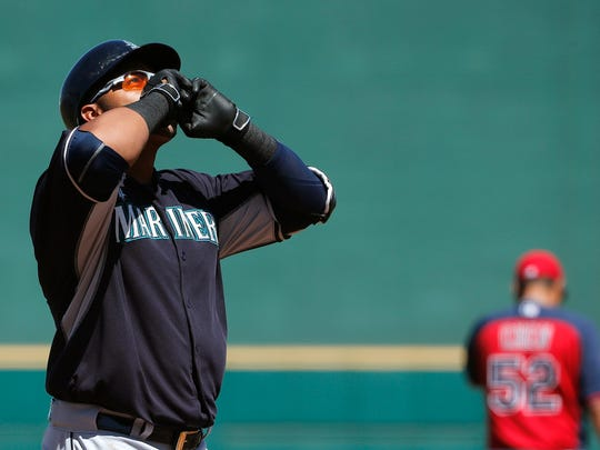 Seattle Mariners' Nelson Cruz, left, looks to the sky as he arrives at home plate after hitting a two-run home run against Cleveland Indians' Bruce Chen, right, during the first inning of a spring training baseball game Tuesday, March 31, 2015, in Goodyear, Ariz. (AP Photo/Ross D. Franklin)