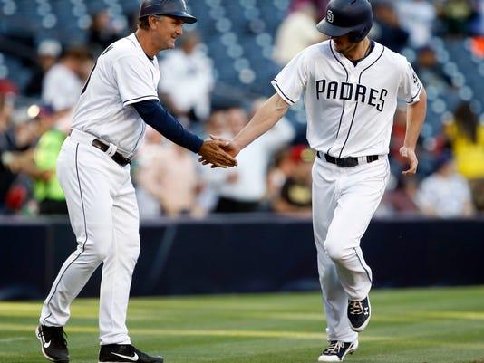 San Diego Padres third base coach Glenn Hoffman, left, congratulates Wil Myers for hitting a solo home run against the Arizona Diamondbacks during the first inning of a baseball game in San Diego, Thursday, April 20, 2017. (AP Photo/Alex Gallardo)