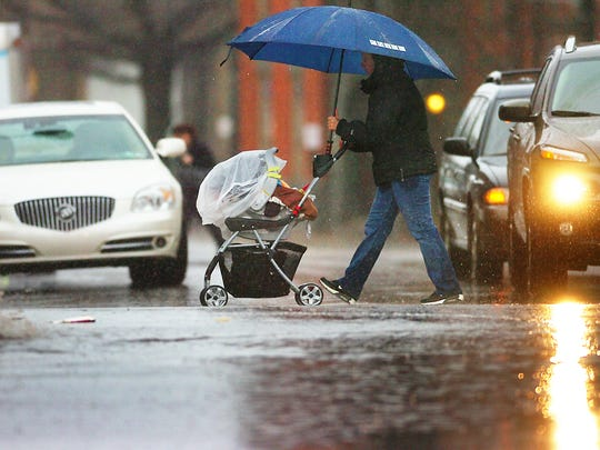 A pedestrian walks with a baby stroller in the rain
