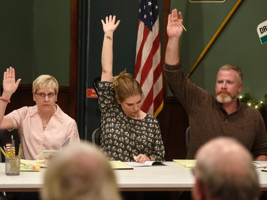 "GREAT Theatre actors raise their hands to vote while performing a scene from ""Twelve Angry Jurors"" during a script-in-hand performance Thursday, Jan. 19, at Jimmy's Pour House in Sauk Rapids."