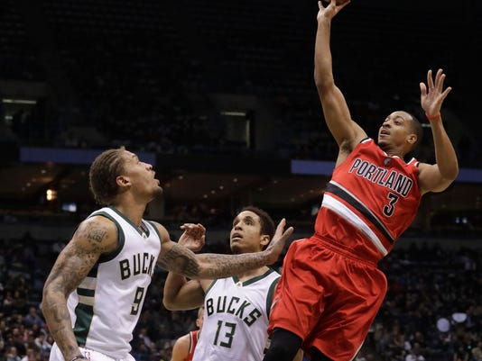 Portland Trail Blazers' C.J. McCollum shoots over Milwaukee Bucks' Michael Beasley (9) and Malcolm Brogdon (13) during the first half of an NBA basketball game Wednesday, Dec. 7, 2016, in Milwaukee. (AP Photo/Morry Gash)