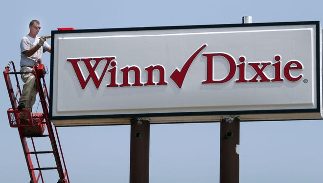 Mark Moore, of BriteLite Signs, paints a sign with the Winn-Dixie logo in this 2006 file photo