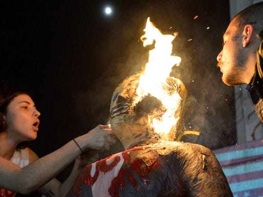 In this Nov. 9, 2016 photo, a woman sets fire to an effigy of Donald Trump during an anti-Trump protest at Lee Circle in New Orleans.