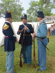 Soldiers from different military origins confer on the ground of Fort Stanton.