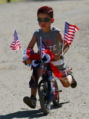 Jaydn Serna rides his bike on Monday during Bloomfield's annual Fourth of July parade.