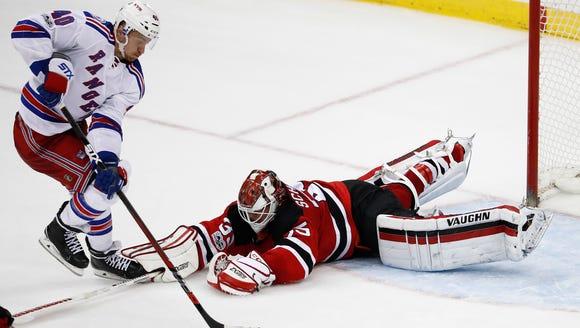 New Jersey Devils goalie Cory Schneider, right, dives