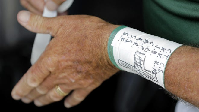 Santa Fe High School baseball coach Ronnie Wolf wears the initials of the school shooting victims on his wrist before a baseball game against Kingwood Park High School in Deer Park, Texas, Saturday, May 19, 2018.