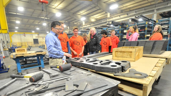 Senior project engineer Chay Her, left, takes John Muir Middle School students on a tour of Schuette Metals' facility in Rothschild in 2014. The company is involved in promoting manufacturing careers among young people.