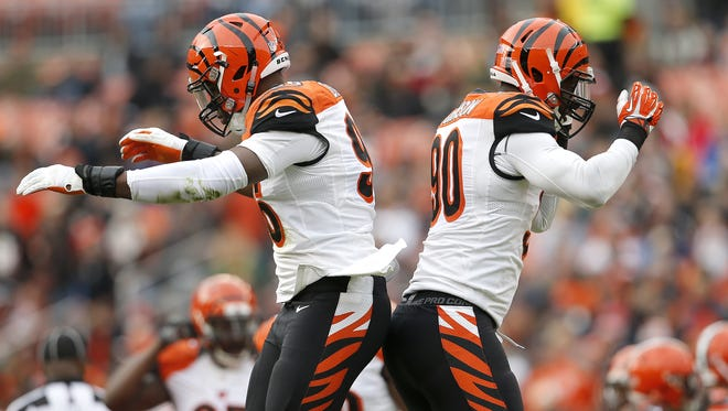 Cincinnati Bengals defensive end Carlos Dunlap (96), left, and Cincinnati Bengals defensive end Michael Johnson (90) celebrate after Johnson's sack in the second quarter during the Week 13 NFL game between the Cincinnati Bengals and the Cleveland Browns, Sunday, Dec. 6, 2015, at FirstEnergy Stadium in Cleveland. The Bengals lead 20-3 at halftime.