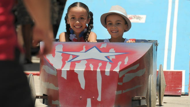 Kamila Nieves and her brother Abrian ride one of the box cars during Saturday's Soaked for Autism event at Space Coast Harley-Davidson.