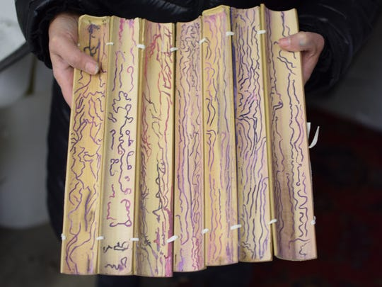 Ellenbogen holds a few of her sketches on bamboo.