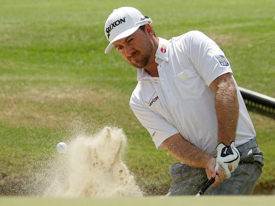 FILE - In this June 13, 2014, file photo, Graeme McDowell, of Northern Ireland, hit out of the bunker on the 16th hole during the second round of the U.S. Open golf tournament in Pinehurst, N.C. McDowell is basking in his latest title: Daddy. A father for all of eight days, McDowell returned to the golf course this week to refocus on his day job, which includes a shot at $10 million. (AP Photo/Charlie Riedel, File)