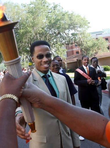 Former FAMU student body president Jomo Bellard hands off the  ceremonial torch during Friday's comemoration of the 50th anniversary of the Tallahassee Bus Boycott.