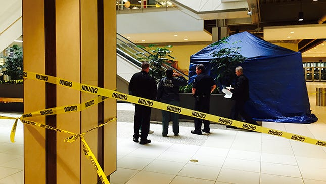 Clarkstown, N.Y., police and Palisades Center Mall personnel talk with an investigator from the Medical Examiner's Office about a man who fell to his death from the third-floor escalators Thursday, Oct. 30, 2014.
